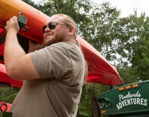a photo of staff member Steve Luell loading a kayak on a trailer